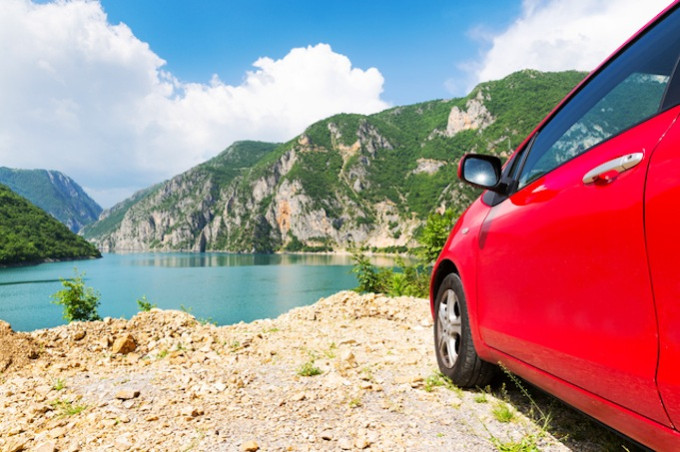 Travel car against mountains and sea